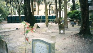 Bare ground and a gravestone with a plate inset. Photograph by Kathleen Rhoads.